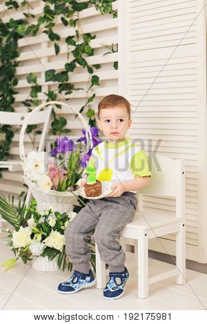 Happy little kid boy celebrating his birthday holds piece of cake, indoor. Birthday party for children. Carefree childhood, happiness. Two years old.