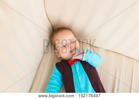 Adorable baby boy with red hair and blue eyes. Newborn child lyling in couch.