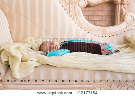 infant baby boy sleeping on the couch