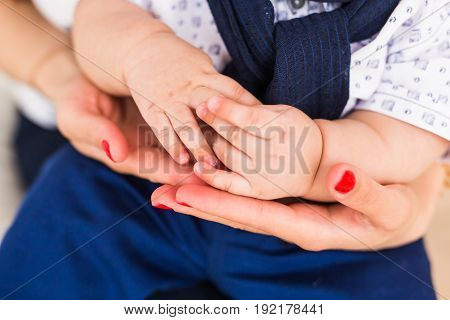 Concept of love and family. Hands of mother and baby closeup.