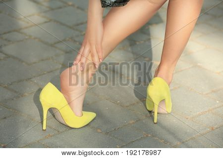 Young woman suffering from leg pain outdoors because of uncomfortable shoes