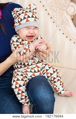 Portrait of crying baby boy in the room