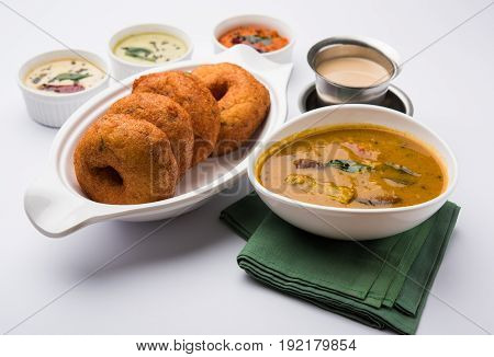 south indian food called vada sambar or sambar vada or wada, served with coconut, green and red chutney over fresg banana leaf, selective focus