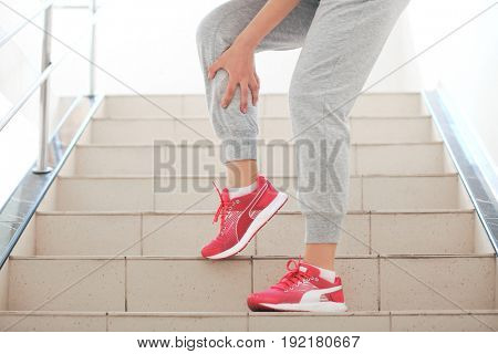 Young woman suffering from pain in leg indoors