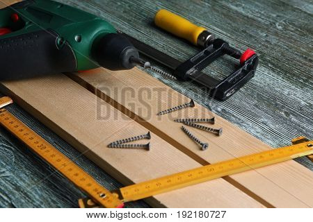 Set of tools and wooden boards on table in carpenter's workshop, closeup