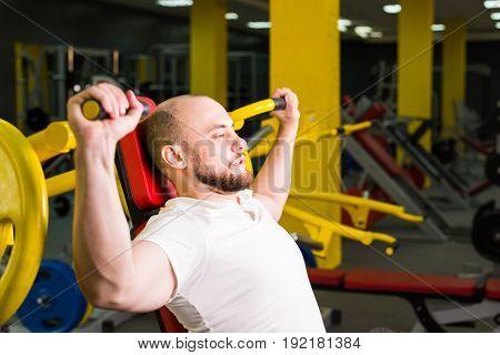 handsome bodybuilder works out excercise in gym.