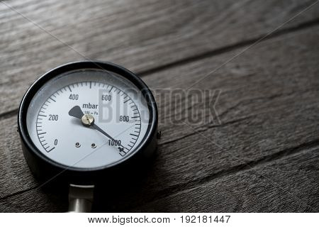 pressure gauge on wood background, close up