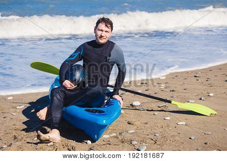 Man with kayak on the beach in sunny day