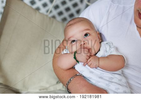 Asian infant baby boy in father's hands.