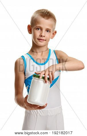 Portrait of little boy in sportswear holding jar with food supplement