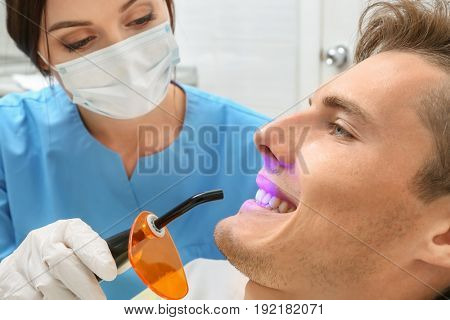 Dentist examining patient teeth in clinic