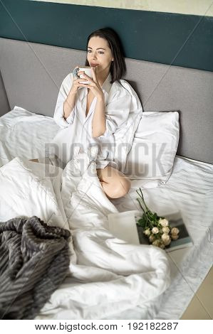 Joyful girl sits on the bed and leans on the white pillows. She holds a cup in her hands and looks forward. Woman wears a white shirt. Bouquet of flowers lies next to her. Closeup. Vertical.