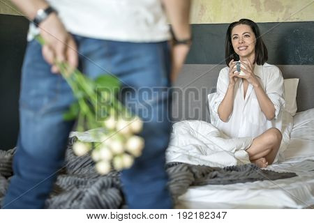 Man in blue jeans and white T-shirt holds a bouquet of roses behind his back. He stands opposite his smiling girlfriend in a white shirt who sits on the bed with a cup in the hands. Closeup.