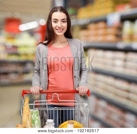 Young woman with market trolley at supermarket