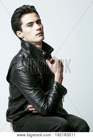 young handsome man, leather jacket, emotional posing, white background, modern guy, lifestyle people concept close up
