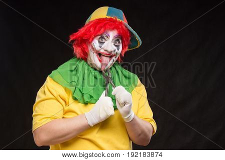 Evil scary clown with red hair on a black background