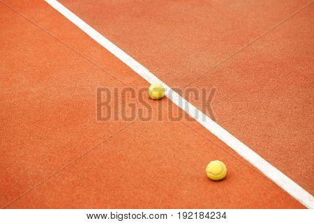 Two yellow tennis balls lie on the tennis court. The concept of sport.