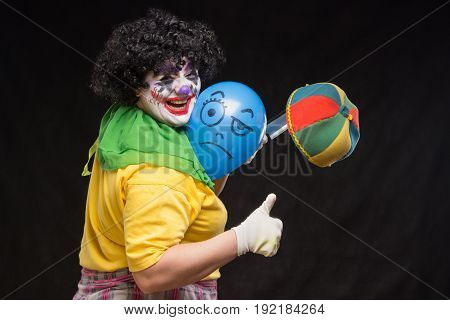 Angry ugly clown wants to kill a balloon in a cap on a black background
