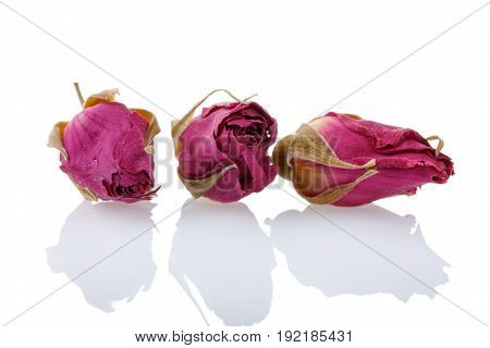 Close-up of dry red rose buds. Healthy herbal tea Isolated on white background