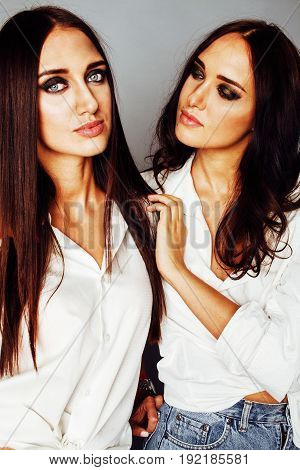 two twin sisters posing, making photo selfie, dressed same white shirt, diverse hairstyle friends, lifestyle people concept