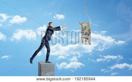 A small businessman standing on a concrete column and catching a dollar bill caught on a metal hook. Business and success. Bait and switch. Business strategies.