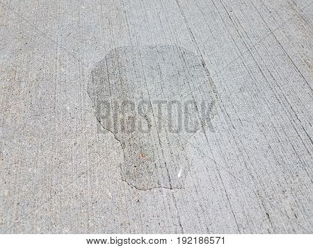 small water puddle on textured grey cement closeup