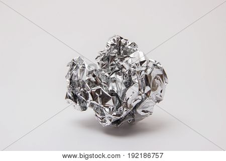 Shiny foil color steel crumpled into a ball on a white background