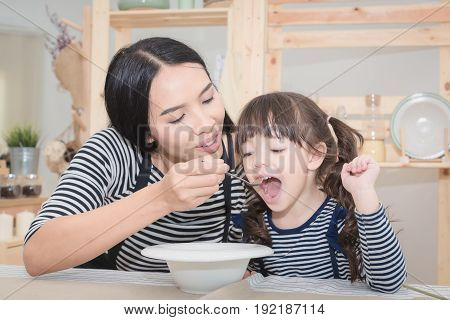 Happy Family Of Asian Mom Feeding Healthy Breakfast To Her Cute Daughter In The Morning. Photo Serie