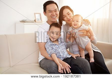 Portrait of happy Asian family with two children posing on sofa at home looking at camera in sunlight