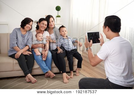 Portrait of big Asian family posing for photo at home, all smiling happily looking at father holding digital tablet
