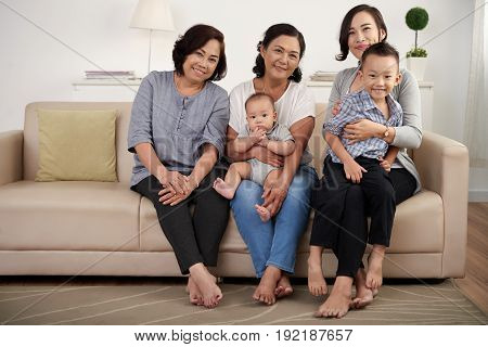 Portrait of  Asian family posing for photo at home, holding two children and  all smiling happily looking at camera in living room