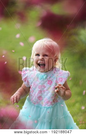 A happy and beautiful little two year old toddler girl is looking up and smiling as the pink flower petals fall off the branches of a blooming Prairie Fire Crabapple tree on a spring day.