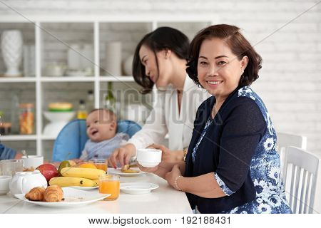 Portrait of mature Asian woman sitting at dining table with family and looking at camera, smiling