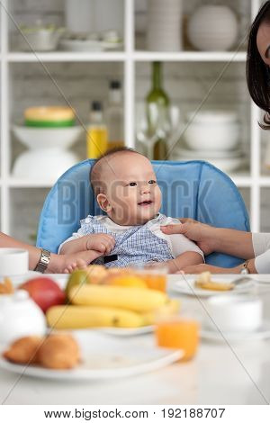Portrait of adorable Asian baby boy smiling, sitting in little chair with family at dining table during breakfast