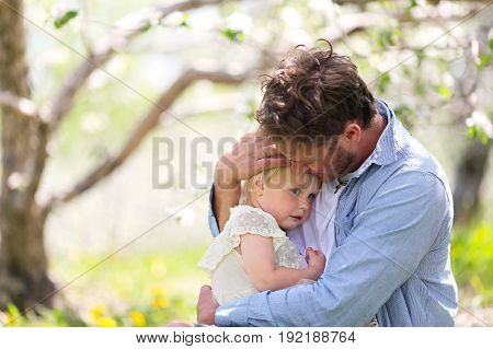 Father Holding And Comforting Sad Baby Daughter