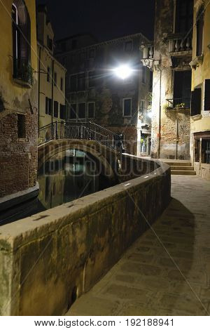 night landscape with the image of bridge over a channel in Venice, Italy