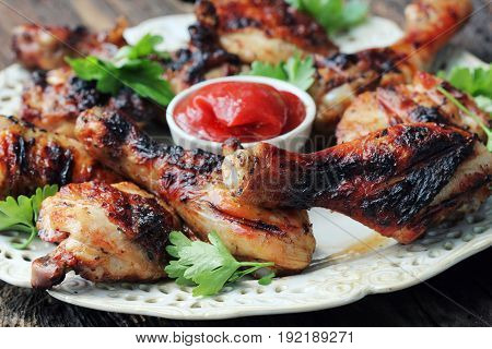 Grilled chicken legs on wooden table served on white plate with coriander .