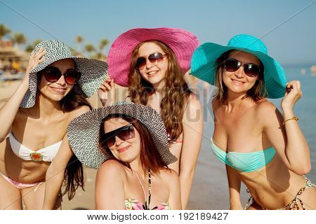 Beautiful slender young girls in bathing suits, hats and sunglasses are having fun smiling at the camera on the beach