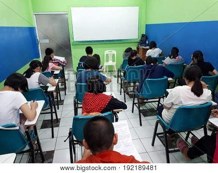 Young Asian students studying on weekends in a small class of a tutorial school