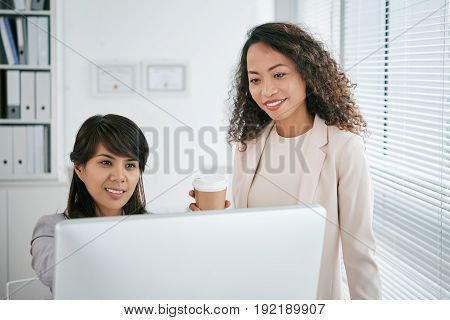 Smiling middle-aged managers gathered together in front of computer and making necessary corrections in version of document