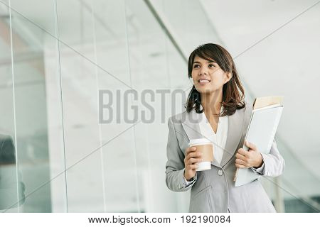 Waist-up portrait of confident Asian white collar worker with cup of coffee and documents in hands standing in modern office lobby and looking away dreamily.