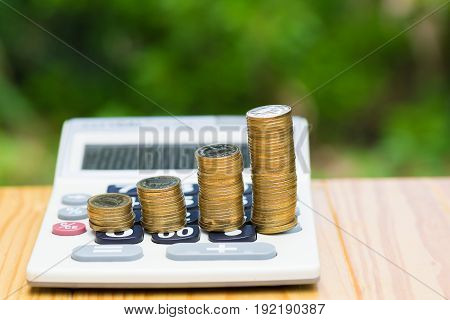 Growing Coins And Calculator On Wood With Green Tree Bokeh Background.
