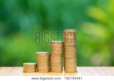Growing Coins Stacks With Green Tree Bokeh Background. Financial Growth, Saving Money, Business Fina
