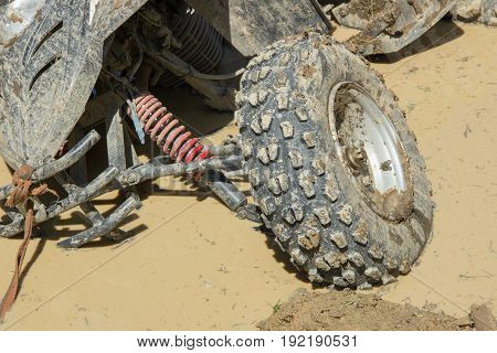 Large dirty ATV stuck in a brown puddle on a forest road