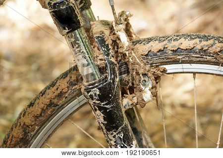Mountain bike wheel brake and suspension fork covered with mud/ Riding a bike through wet and muddy road concept