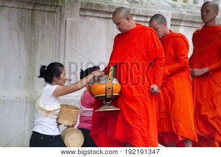 Luang Prabang Laos - Aug 2012: Buddhist monks collecting alms in the morning. The tradition of giving alms to monks in Luang Prabang has been extended to tourists.
