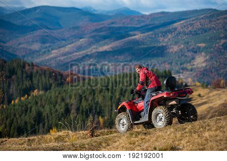Man Riding On Red Quad Bike, Looking To The Camera At Autumn Sunny Day. Landscape Of Mountains, Fore