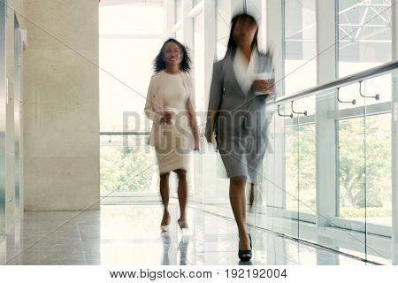 Cheerful businesswomen with paper cups of coffee in hands walking down office corridor with panoramic windows, shot in motion