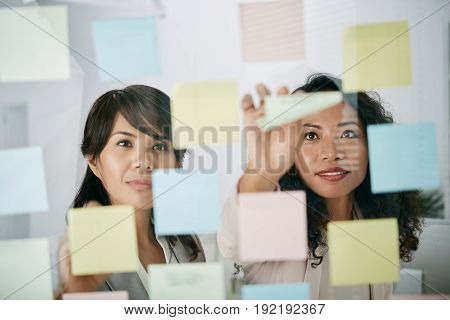 Attractive Asian managers using sticky notes in order to share ideas with each other, view through glass board