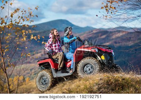 Happy Women Driving Atv On Snowy Hills In Winter Clothing On The Background Of Mighty Mountains And